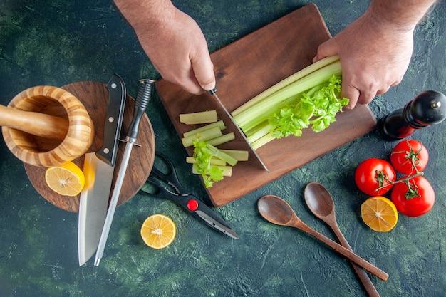 暗いテーブルでセロリを切る男性料理人の上面図サラダダイエット食事カラー写真食品健康