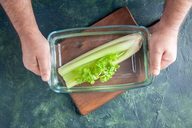 暗いテーブルにセロリとプレートを保持している上面図男性料理人サラダダイエット食事カラー写真食品健康