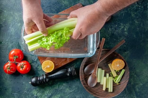 暗いテーブルの上の水でプレートからセロリを取り出す男性料理人の上面図サラダダイエット食事写真食品健康色