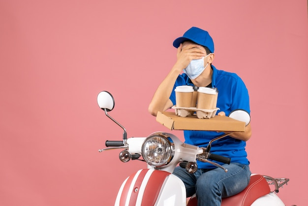 Top view of male delivery person in mask wearing hat sitting on scooter delivering orders closing his eye