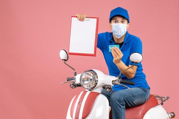Vista dall'alto del fattorino maschio in maschera che indossa un cappello seduto su uno scooter che mostra documento e carta di credito su sfondo color pesca pastello
