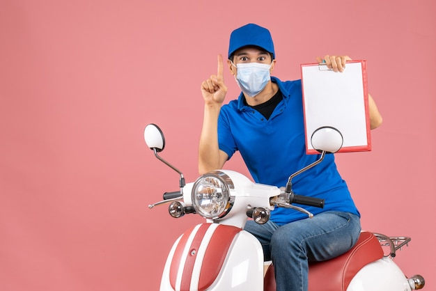 Top view of male delivery person in mask wearing hat sitting on scooter showing document pointing up on pastel peach background