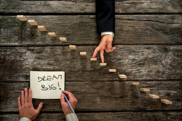 Top view of male hand writing an encouraging message dream big in a notepad as a businessman walks his fingers up wooden pegs resembling staircase.