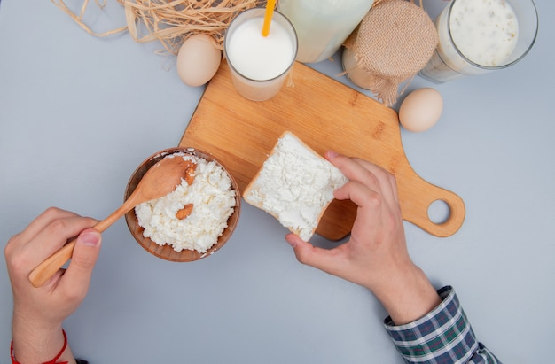 Top view of male hands holding bread slice smeared with cottage cheese and spoon with milk on cutting board and eggs yogurt soup cream straw on blue table