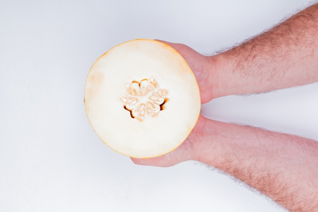 Top view of male hands holding melon on white background with copy space