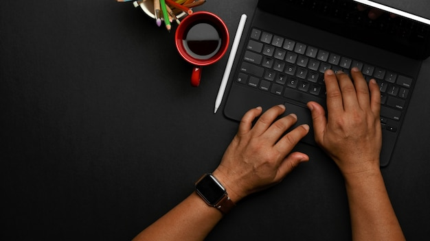 Top view of male hands typing on tablet keyboard on black table with coffee cup