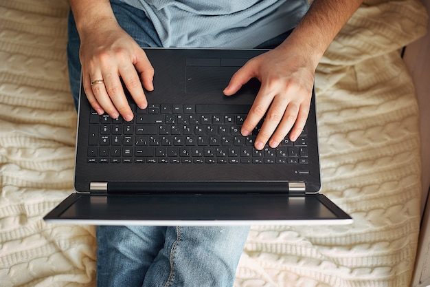 Top view of male hands using modern laptop, close up of young man working at home and using notebook computer