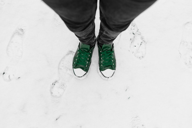 Top view of male legs wearing black jeans and green vintage sneakers shoes, standing on snow outdoor. foots selfie.