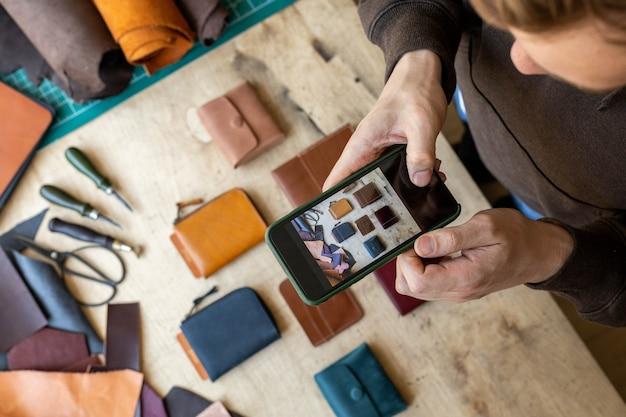 Вид сверху мужские руки кожевника, фотографирующие эксклюзивные аксессуары для кожгалантереи кожевенной мастерской