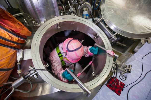 상위 뷰 남성 작업자는 탱크 스테인리스 화학 구역 밀폐 공간 안전 송풍기 신선한 공기로 계단을 올라