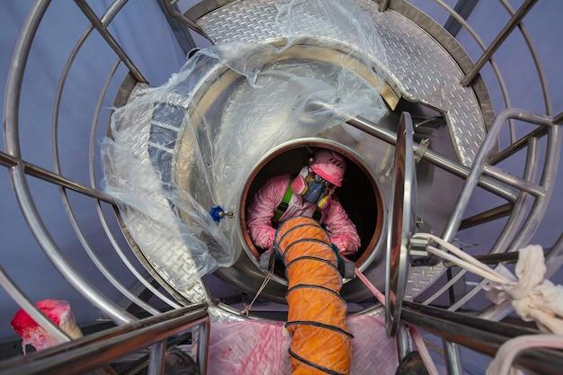 상위 뷰 남성 작업자는 탱크 스테인리스 화학 영역 밀폐 공간 안전 송풍기 신선한 공기로 계단을 올라