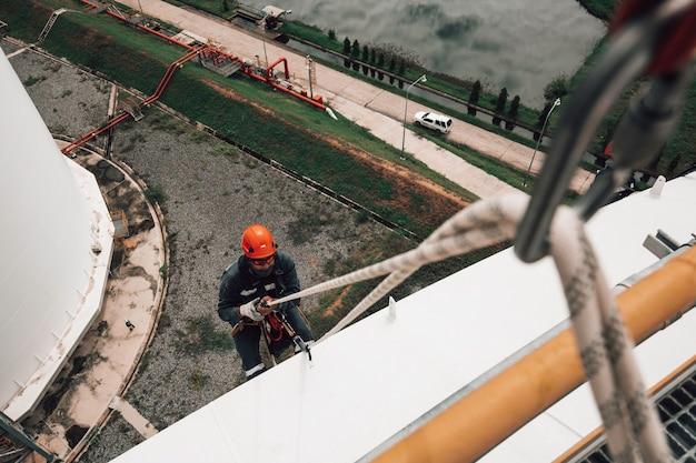 상단 보기 남성 작업자 아래로 높이 탱크 쉘 플레이트 로프 사다리 액세스 두께 저장 탱크 가스 프로판의 안전 검사.