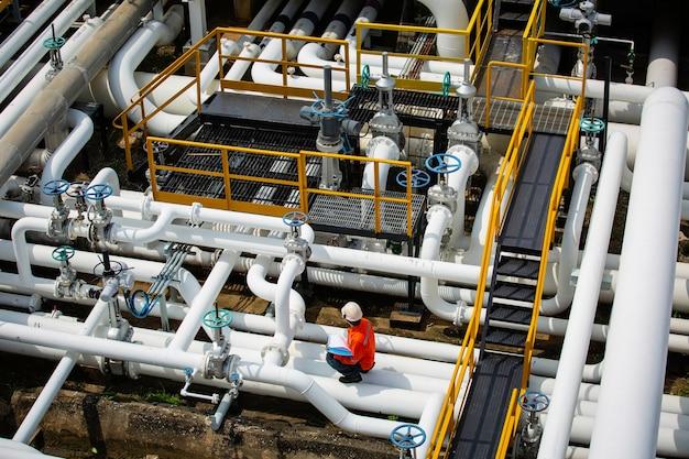 Вид сверху мужской рабочий осмотр на клапане трубопровода визуальной проверки нефтяной и газовой промышленности