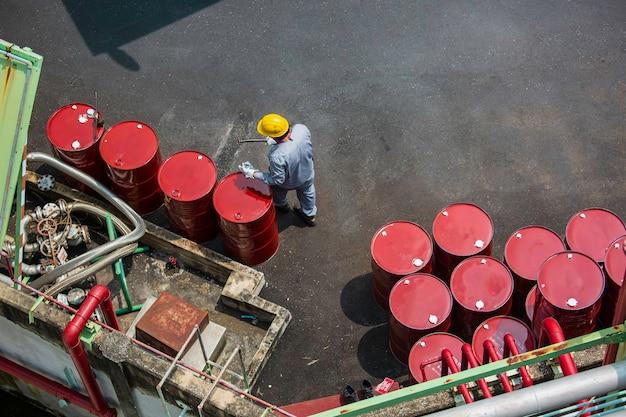상위 뷰 남성 작업자 검사 기록 드럼 오일 스톡 배럴은 업계에서 빨간색 수직 또는 화학 물질입니다.