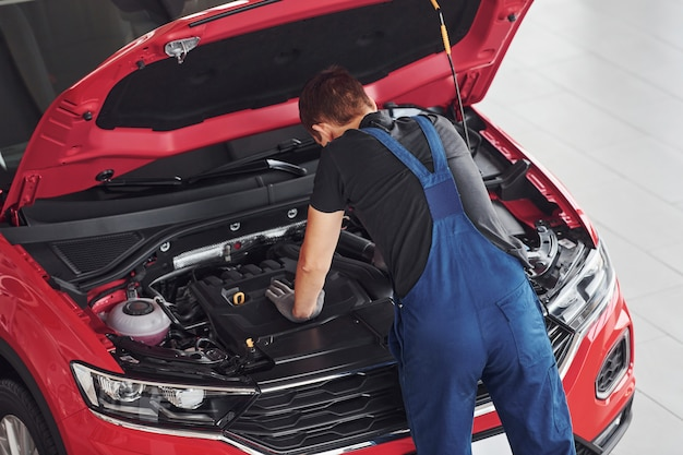 Top view of male worker in uniform that repairs red automobile