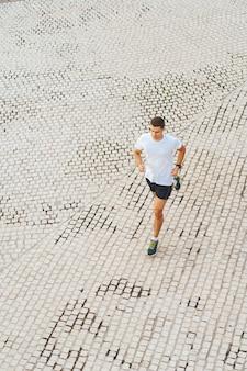 Top view of man athlete wearing sportswear run in park at summer morning.