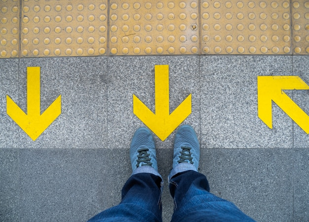 Top view of man feet standing over arrow symbol on subway platform.