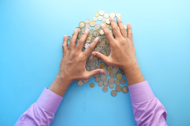Top view of man hand counting coins on color background