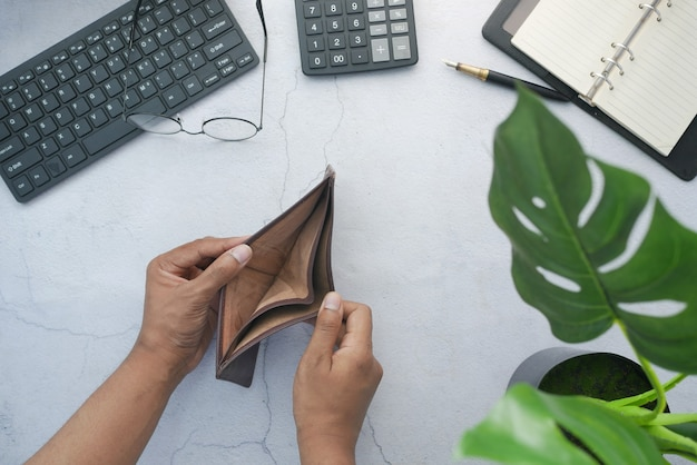 Top view of man hand open an empty wallet on table