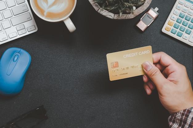 Вид сверху человек, держащий кредитную карту и на столе
