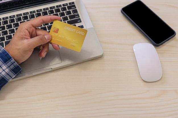 Вид сверху человек, держащий кредитную карту и одетый в синюю клетчатую рубашку на столе. портативный компьютер и смартфон. интернет-магазин, оплата кредитной картой