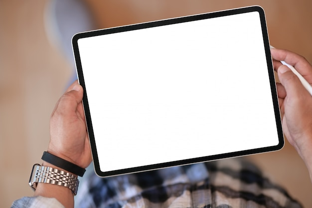 Top view of a man holding pencil and mockup blank screen digital tablet device