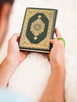 Top view of a man holding quran
