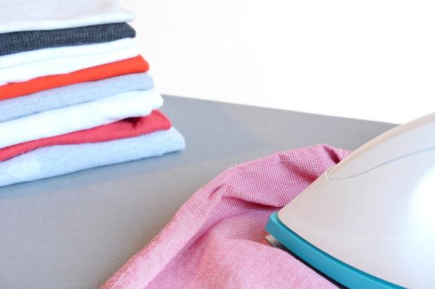 Top view of man ironing pink  shirt on ironing board