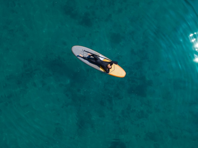 top view man laying on surfboard