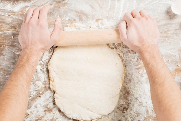 Top view of man making pizza dough