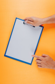 Top view man pointing to clipboard while holding it on orange