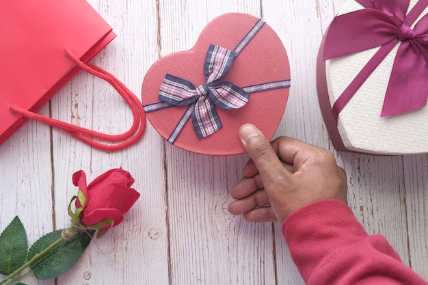 Top view of man's hand holding a gift box on table