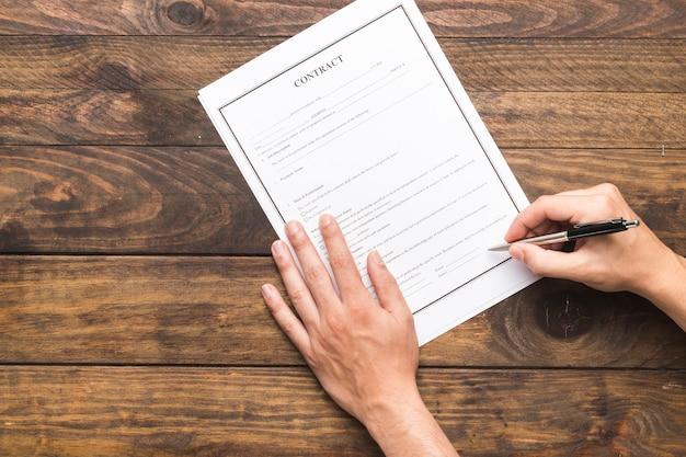 Человек взгляд сверху подписывая контракт на деревянном столе