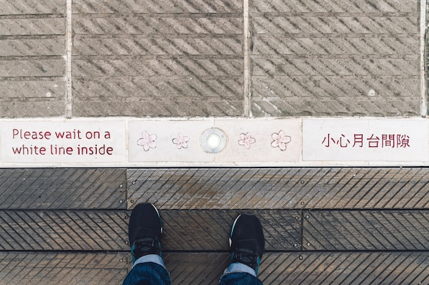 Top view of a man standing at the zhaoping railway station platform with warning words in english and chinese language and decorated flowers in alishan, taiwan.