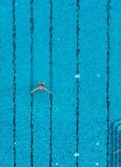 Вид сверху человек плавание в бассейне. фон для спорта и отдыха в отпуске.