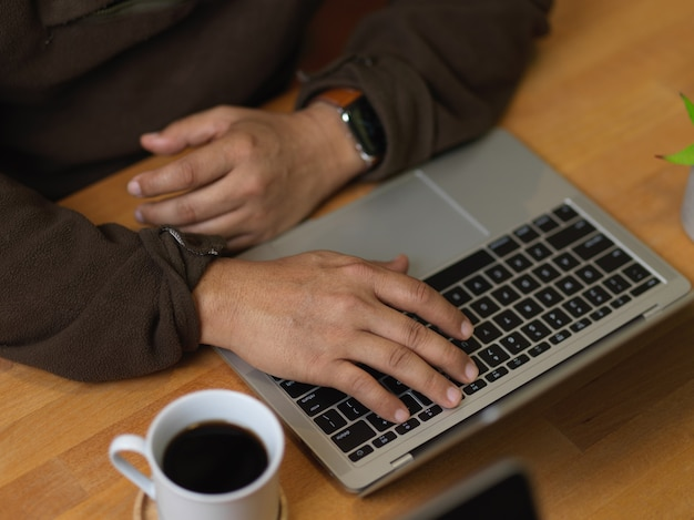 Top view of man typing on laptop keyboard on wooden table with coffee cup