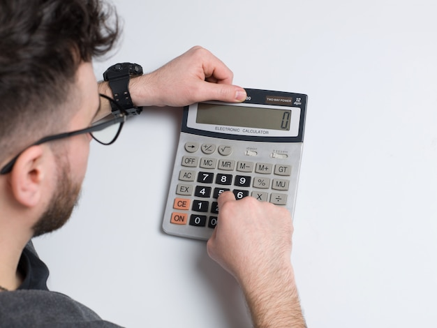 A top view man using calculator on the white desk