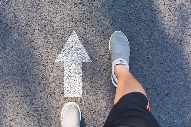 Top view of man wearing white shoes choosing a way marked with white arrows.