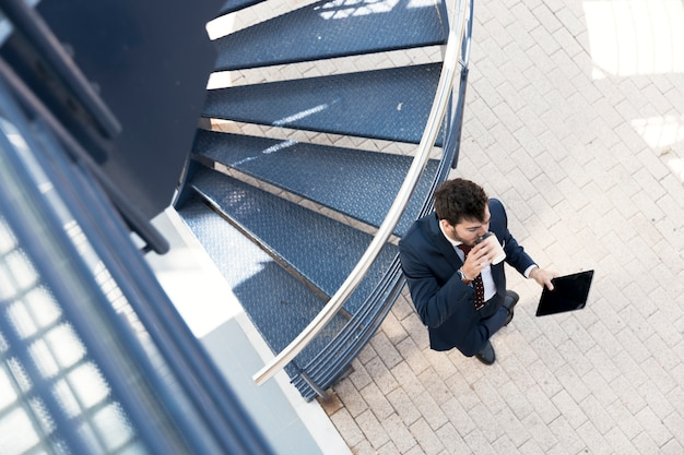 Top view man with tablet drinking coffee near stairs