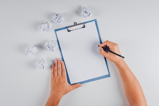 Top view man writing on clipboard with crumpled papers on white