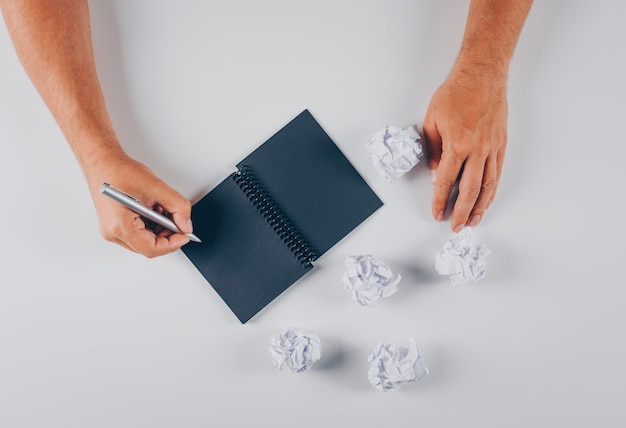 Top view man writing on notepad with crumpled papers on white
