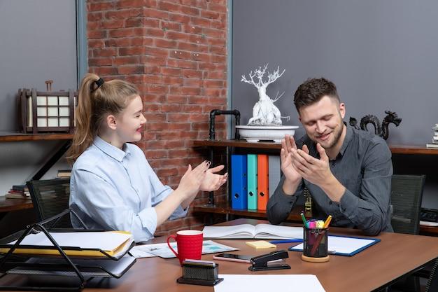 La vista dall'alto del team di gestione seduto al tavolo è arrivata alla negoziazione nella sala riunioni in ufficio