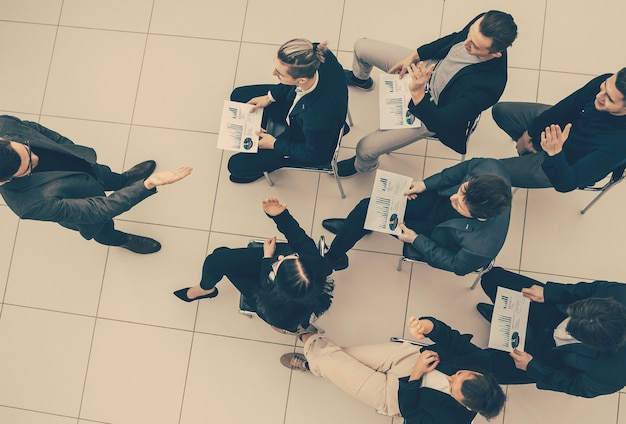 Top view manager asks questions during a business meeting