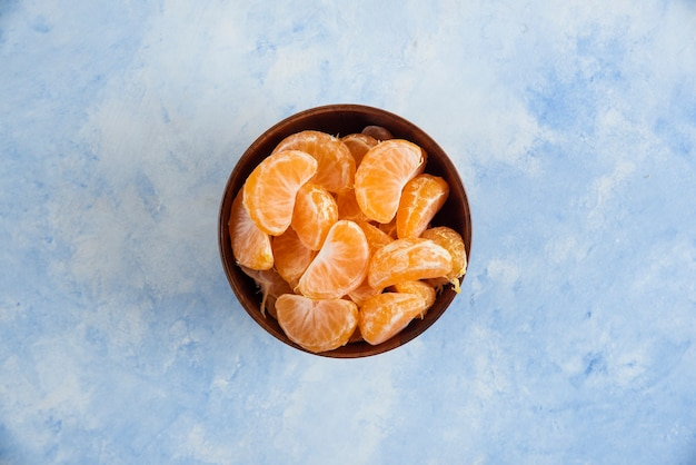 Top view of mandarin slices in wooden bowl on blue surface