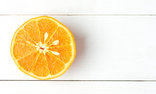 Top view mandarin squeezed slice orange on white wood table with copy space