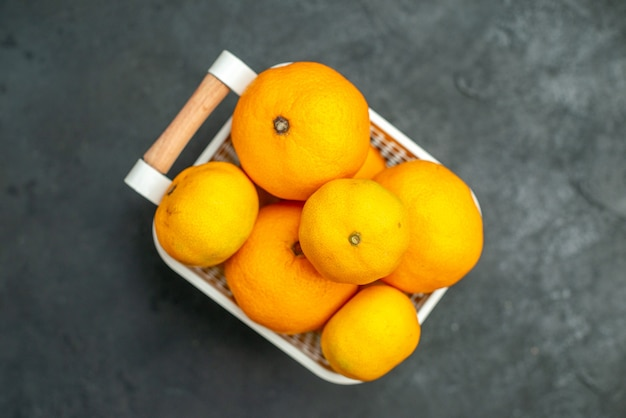 어두운 배경의 플라스틱 바구니에 있는 상위 뷰 만다린과 오렌지