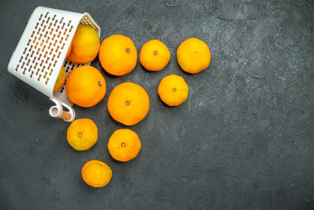 Mandarini e arance vista dall'alto sparsi dal cestino di plastica su sfondo scuro