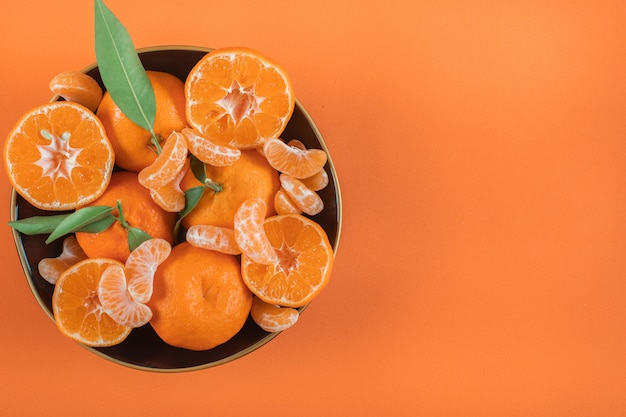 Top view mandarins in plate with copy space on orange surface