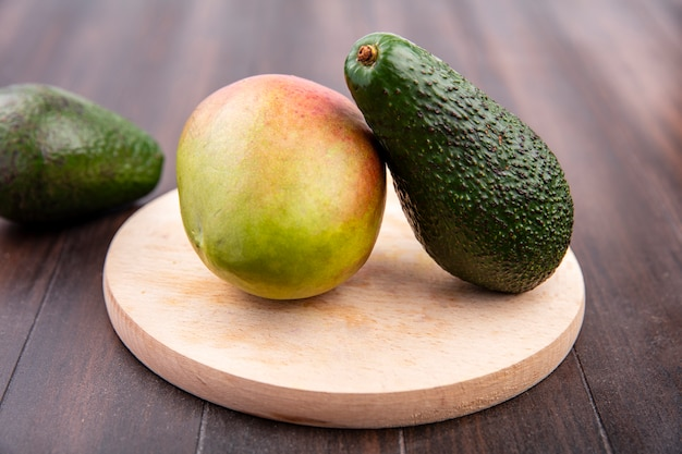 Top view of mango and avocado on a wooden kitchen board on a wooden surface
