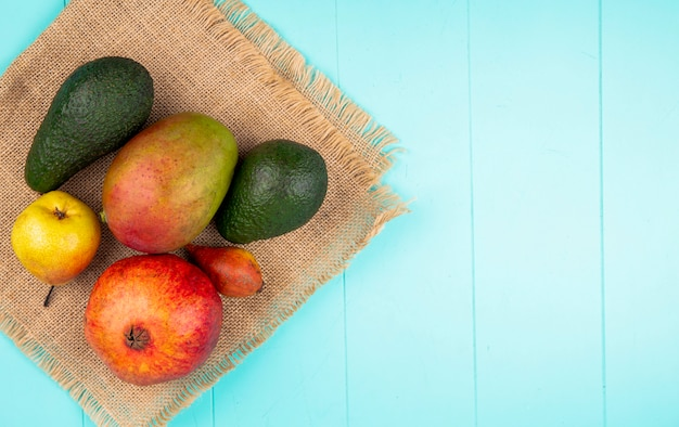 Top view of mango with avocado pear pomegranate on sack cloth on blue surface